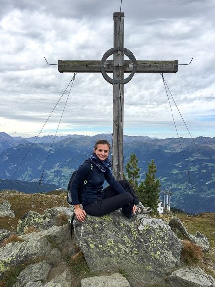 Frau sitzt seitlich vor Gipfelkreuz - bewölkter Himmel - die gegenüberliegenden Berge sind sichtbar