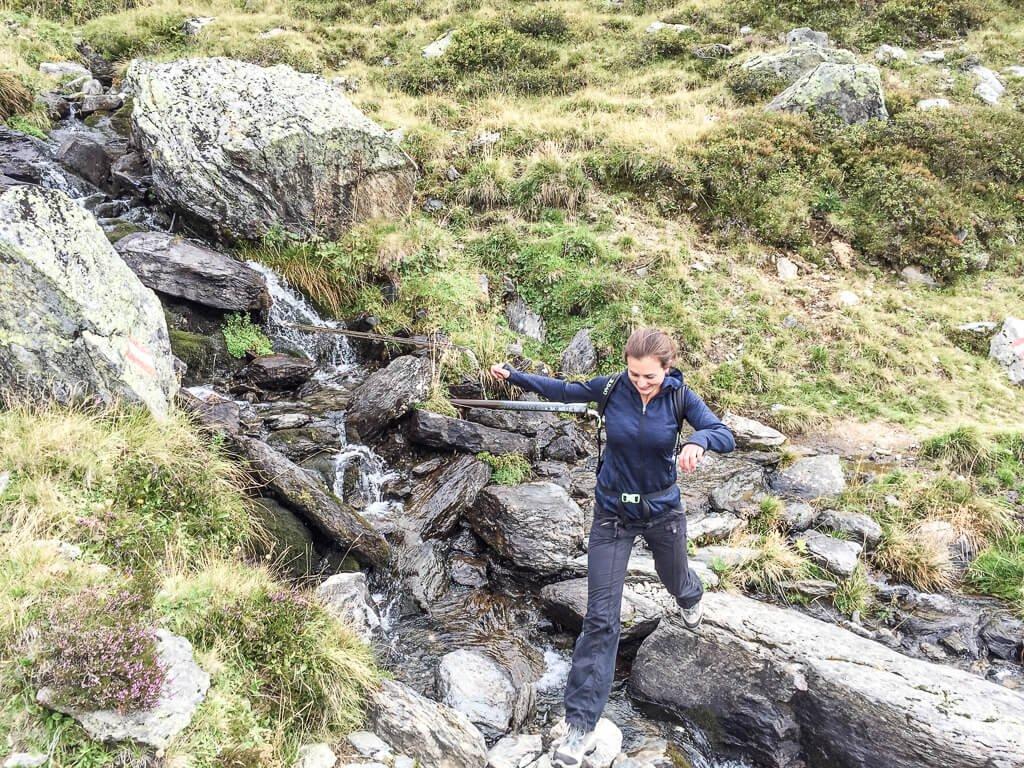 Frau springt am Berg über einen kleinen Bach