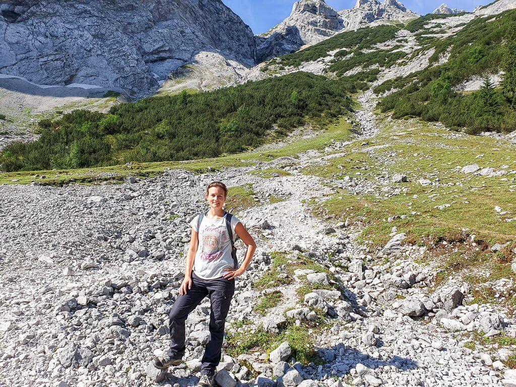 Frau steht auf Geröllfeld, dahinter ein Wanderweg am Berg