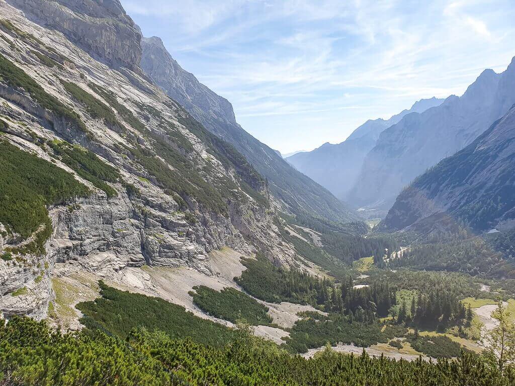 Ausblick in ein grünes Tal, links und im Hintergrund schroffe Berge