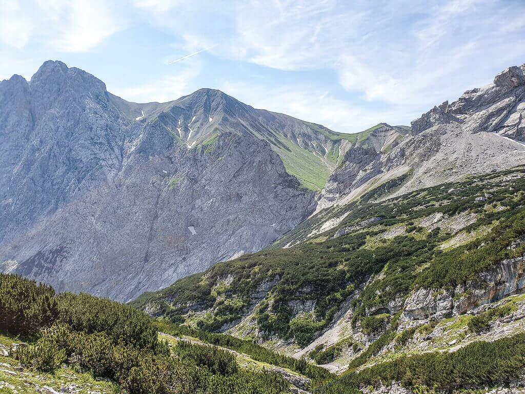 Blick über grüne Hügel auf steinige Berge
