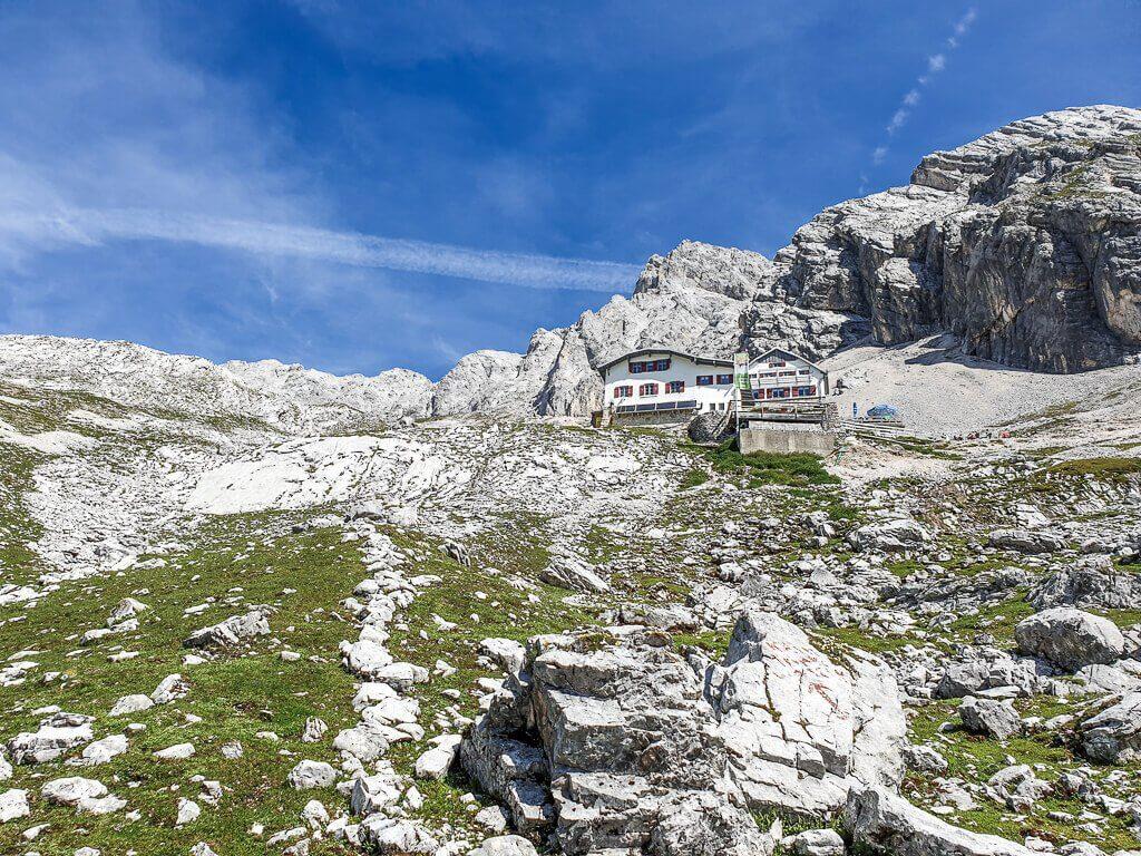 Hütte mitten am Berg zwischen Felsen und grünen Wiesen an der Zugspitze