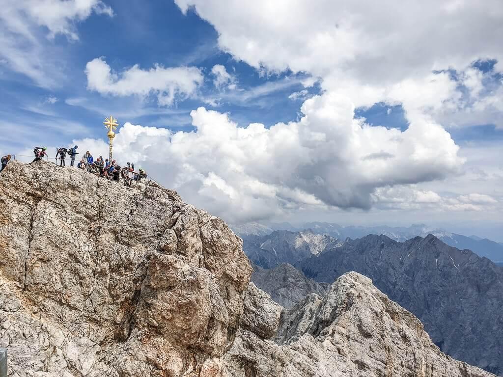 Zugspitze, goldenes Gipfelkreuz auf dem Felsen mit vielen Menschen drumherum