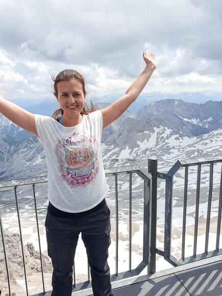 Frau steht mit in die Höhe gereckten Armen vor einem Bergpanorama