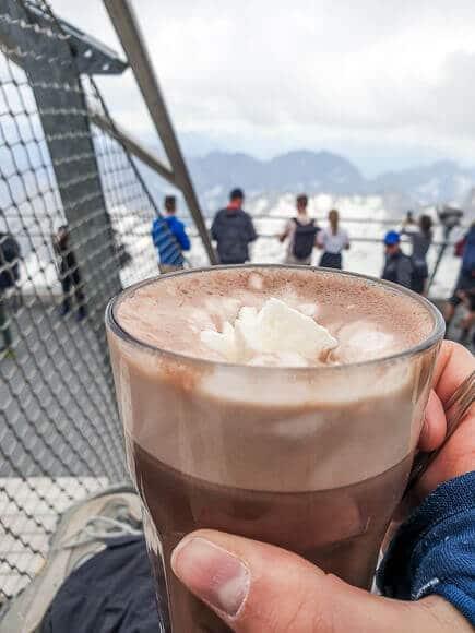 Hand mit heißer Schokolade vor einem Bergpanorama