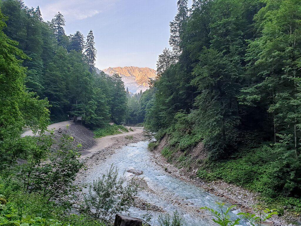 Flussf fließt zwischen Bäumen und Bergen - am Horizont geht die Sonne über den Bergen auf