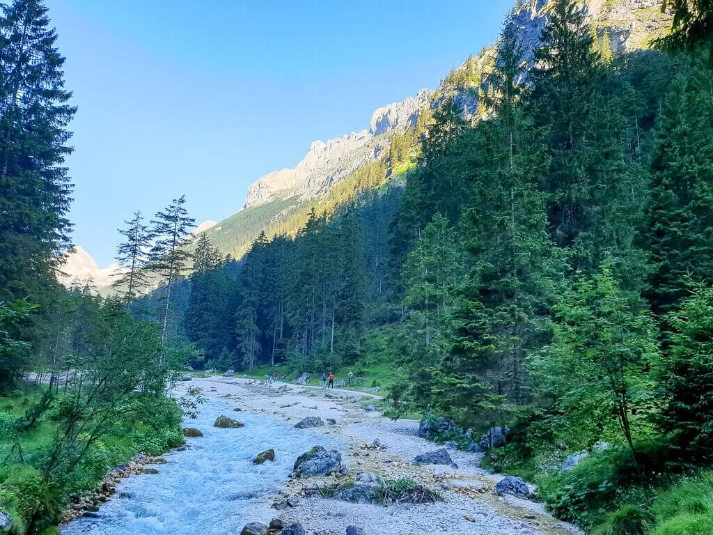 Partnach fließt leuchtend Blau zwischen Steinen und Bäumen in den Bergen