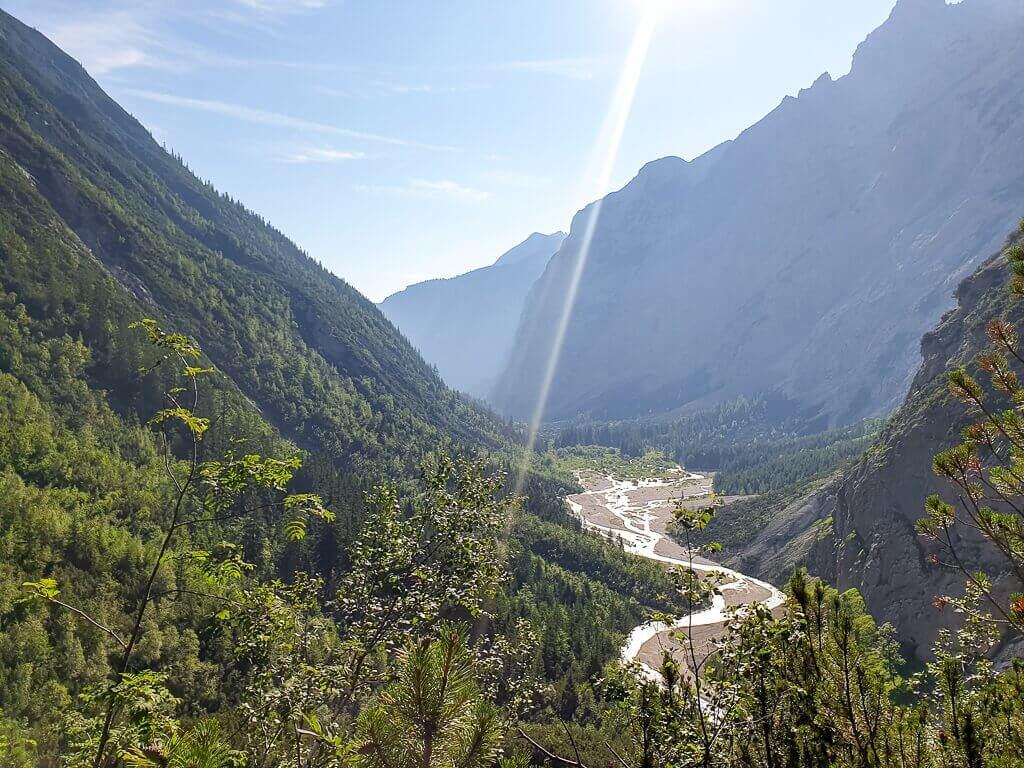 Sonne strahlt am Himmel, darunter ein sich windender Fluss zwischen den Bergen