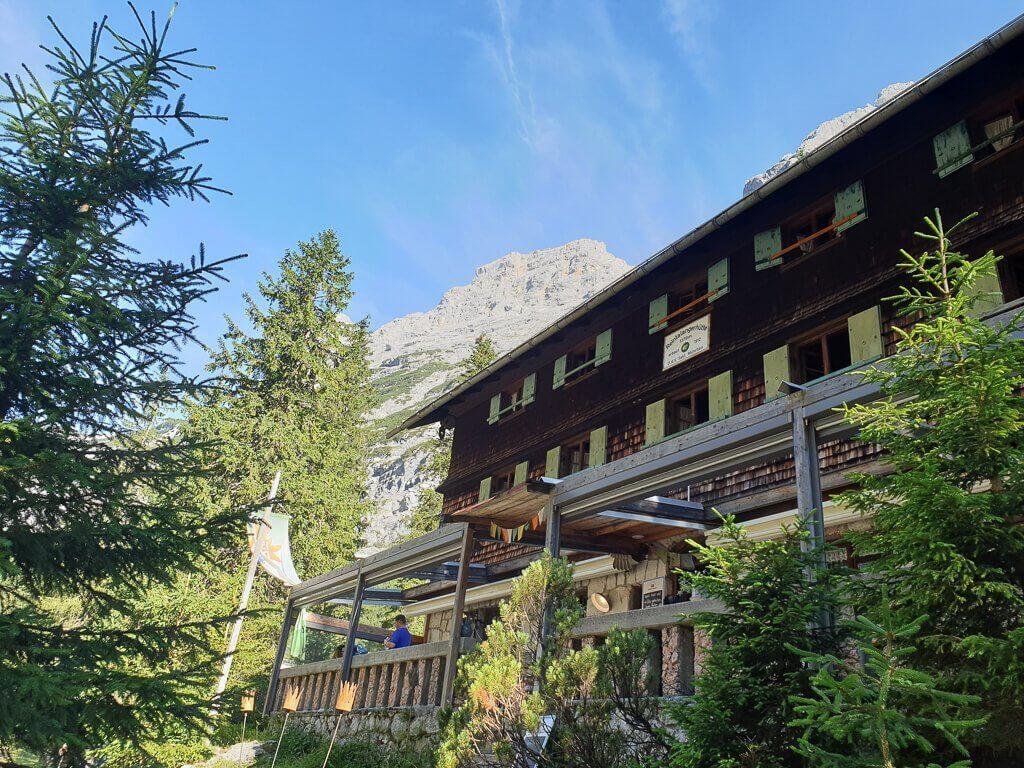 Eine Holzhütte im Wald mit Berg im Hintergrund