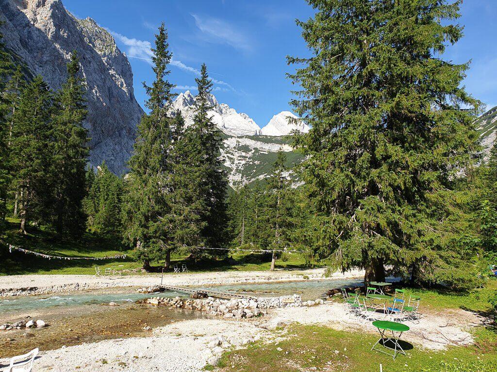 Fluss fließt mittig zwischen einem Kiesbett, auf beiden Seiten hohe Tannen und Berge im Hintergrund