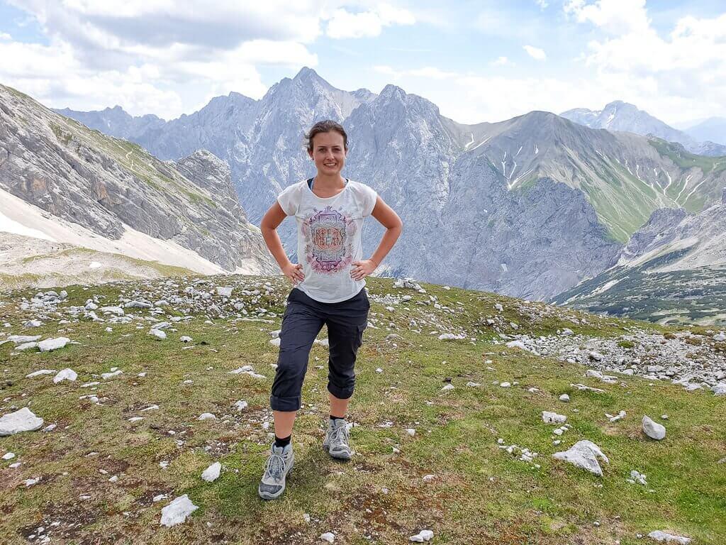 Frau steht auf einer Wiese - im Hintergrund Berggipfel