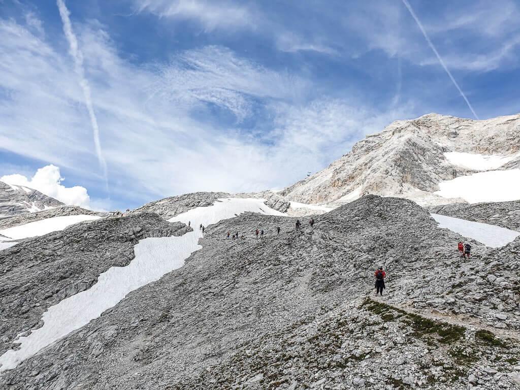 Wanderer auf einem felsigen Berg, dazwischen Schneefelder