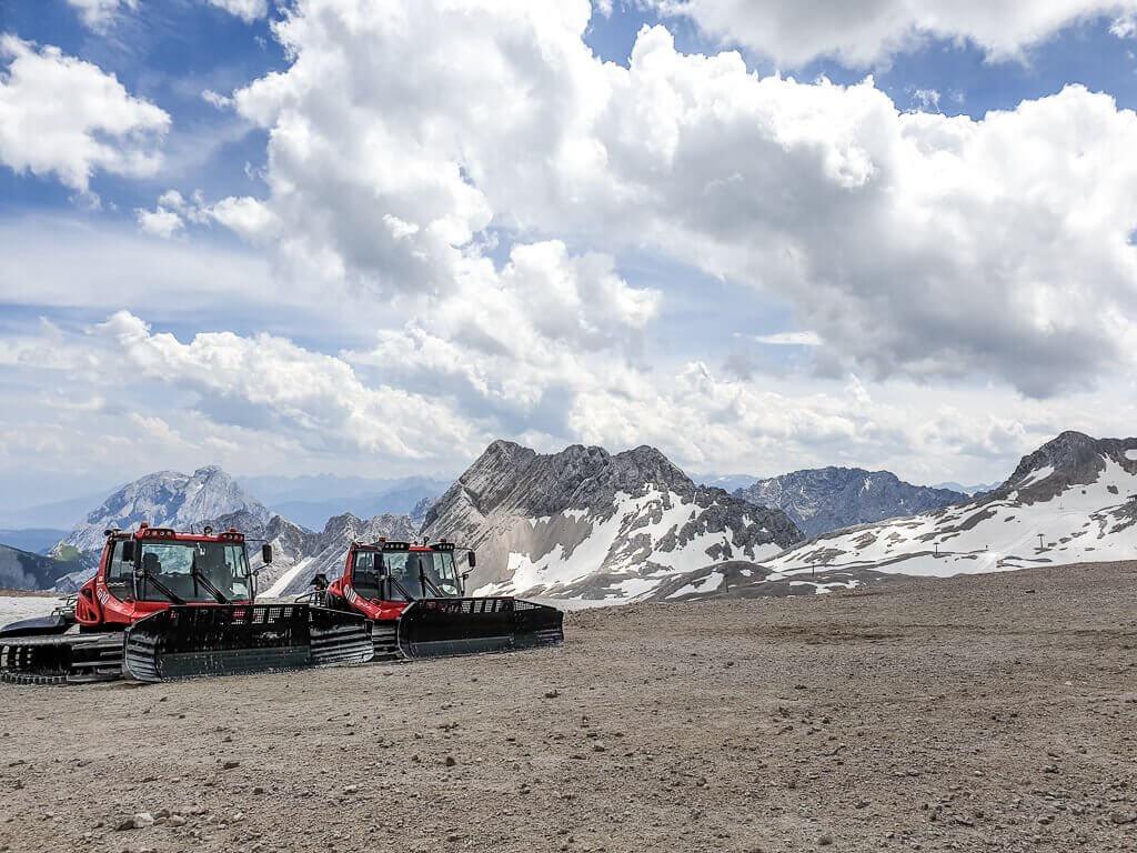 Pistenraupen auf einem Schotterfeld, im Hintergrund schneebedeckte Berge