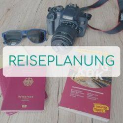 Reiseführer, Reisepass und Kamera liegen auf einem Tisch